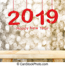 2019 Happy new year hanging over plain wood table top with blur gold sparkling bokeh light, Holiday concept, leave space for adding your design.