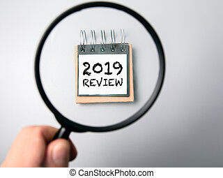 2019 review concept. Man's hand, holding magnifying glass