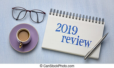 2019 review text in a spiral notebook with a pen, coffee and reading glasses, business year summary and evaluation concept