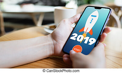 2019 year Rocket start button on mobile phone screen. Business concept.