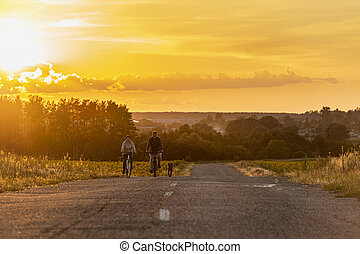 2020-07-15 Bucha, Ukraine. Happy middle-age couple on a bike ride with their dog.
