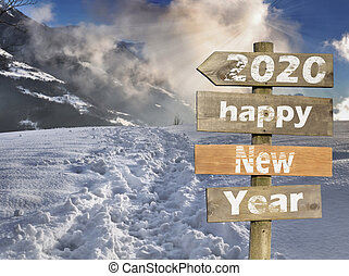 wooden post sign in front of a scenery sunset in snowy mountain
