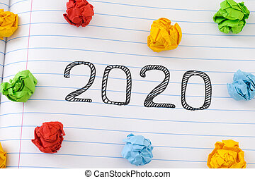 2020 New Year on notebook sheet with some colorful crumpled paper balls around it