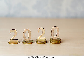 2020 - wooden numbers on stacks of coins on a light background. Creative idea for business growth, tax payment, investment and banking, New year saving money and financial planning concept