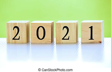 2021 number on wooden block with green background