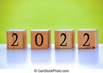 2022 number on wooden block with green background