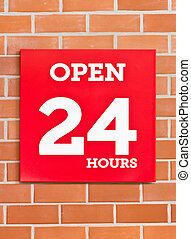 24 hours red signboard on brick background.