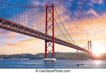 25th April Bridge in Lisbon, Portugal. Famous landmark on river Tagus. Summer sunny landscape with evening dusk sunset sky with clouds and sunlight.