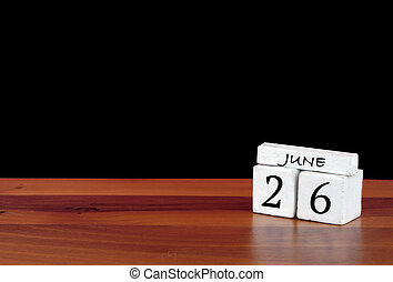 26 June calendar month. 26 days of the month. Reflected calendar on wooden floor with black background