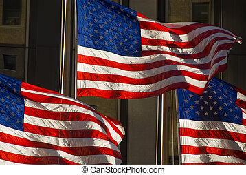 3 american flags against buiding