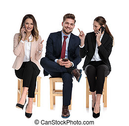 3 businessmen holding their phones, pointing and giving thumb up