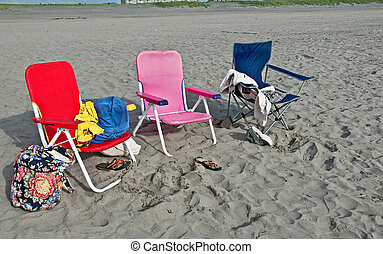 3 Colorful Chairs and Beach Stuff on Sandy Beach