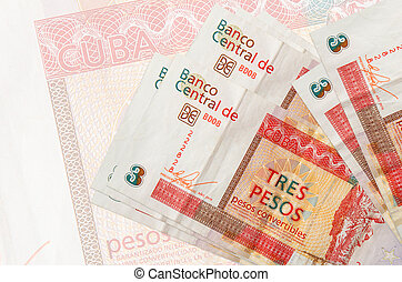 3 cuban pesos convertibles bills lies in stack on background of big semi-transparent banknote. Abstract presentation of national currency