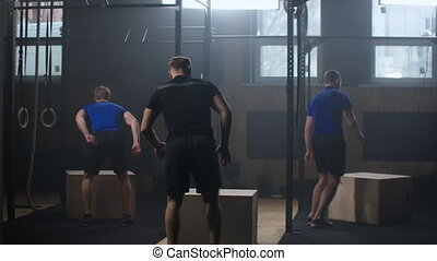 3 fitness man training box jump workout exercise challenge in gym enjoying healthy bodybuilding lifestyle friends practice together slow motion.