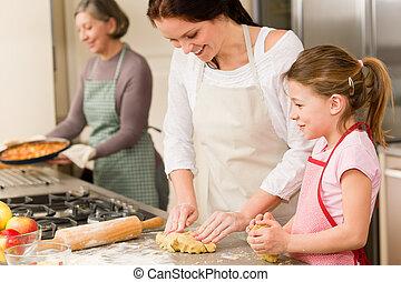 3 generations of women baking apple pies