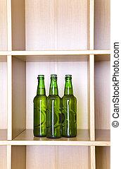 3 green glass bottles on a regiment
