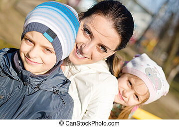 3 people beautiful young mother with two children, son and daughter having fun happy smiling & looking at camera, closeup portrait on spring or autumn outdoors background