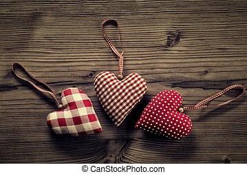 3 pieces of fabric hearts, polka dots , plaid, on wood background