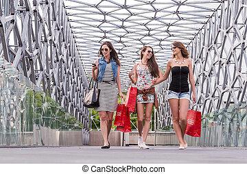 3 Pretty woman walking on the bridge, enjoying the shopping