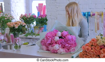 3 shots. Florist wraps flowers in gift paper at flower shop