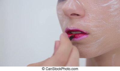 3 shots. Lips painting: professional make-up artist making...