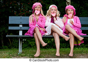 3 Sisters eating a lollipop - Happy children having pink...