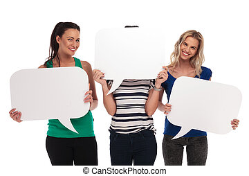 3 smiling women holding speech bubbles, one covering her face