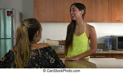 Two female friends at home, relaxing and talking in the kitchen. The girls shake a nutritional supplement and drink a proteic beverage for weight loss. Steadicam shot