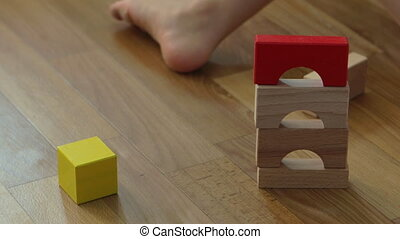 3 years old child boy play with wooden blocks, build house...