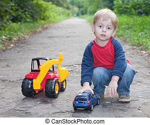 child playing toy car in park