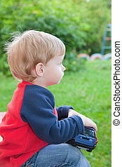 child with toy car in park