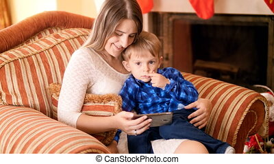 3 years old cute toddler boy sitting with mother in armchair at living room and watching video on screen of mobile phone