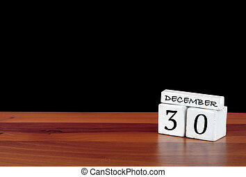 30 December calendar month. 30 days of the month. Reflected calendar on wooden floor with black background