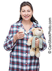 30 year old woman with a glass of milk and a toy in love before going to sleep on a white background