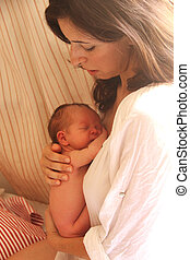 30 years old beautifull mother is talking to her newborn daughte