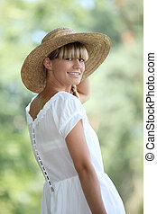 30 years old blonde woman wearing a white dress and a straw hat walking in the nature