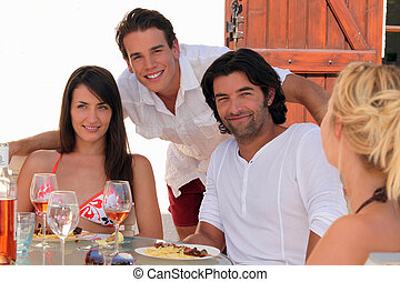 30 years old couple and a 20 years old man behind them posing outside at lunch time, summer scene