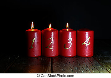 3.Advent. Red Advent candles stand on a wooden floor