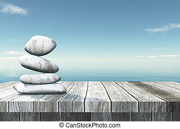 3D balancing pebbles on a wooden table looking out to the ocean