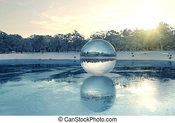 3d, interpretación, de, bola de cristal, en, lago congelado, en, el, tarde, luz del sol