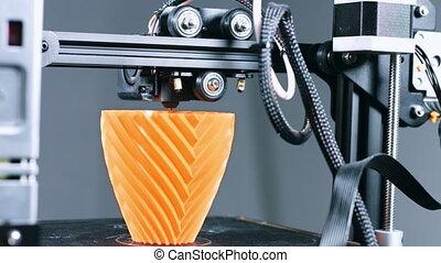 3D Printer printing a vase for home decoration with orange plastic Filament.