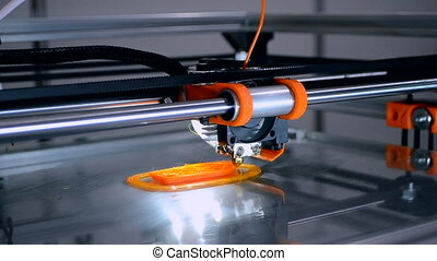3d printer prints orange object close-up. Automatic three dimensional 3D printer printing model from performs plastic. Progressive additive technology for 3d printing. Fused deposition modeling, FDM.
