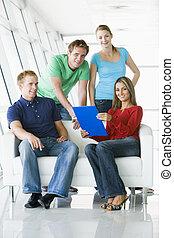4人の人々, 中に, ロビー, で 指すこと, クリップボード, 微笑