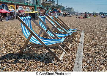 4 deck chairs on Brighton beach