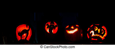 four very scary carve pumpkins lit up against a dark background.