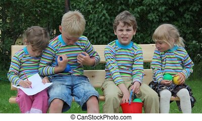 4 kids sitting on bench and playing with balls