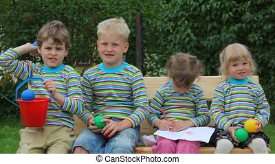 4 kids sitting on bench and throwing balls