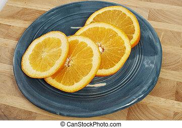 4 orange ( Citrus sinensis ) slices on blue plate