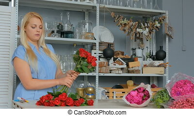 4 shots. Professional florist preparing red roses for...