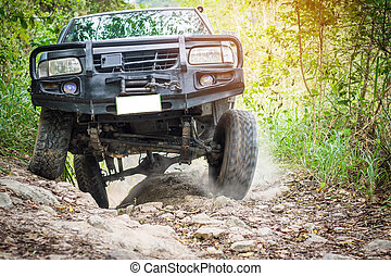 4 wheel drive is climbing on a difficult off-road in mountain forests in Thailand.